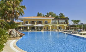 Martinhal Quinta Portugal exterior pool yellow building with arches and balconies overlooking pool with slide