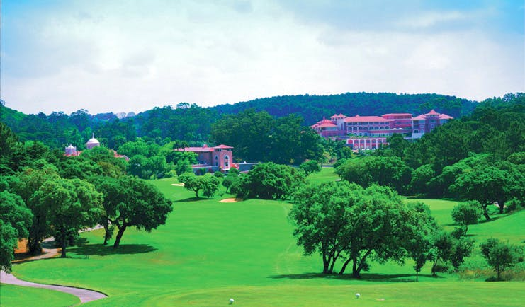 Penha Longa Portugal golf course surrounded by trees and pink building in the distance