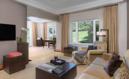 Penha Longa Portugal suite lounge with sofas and chairs and large patio doors