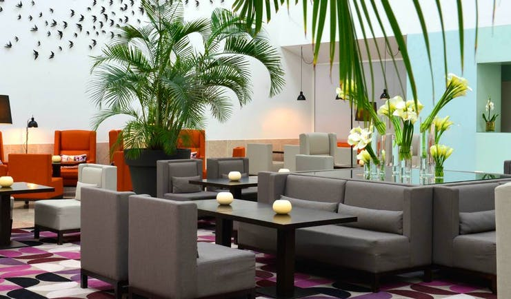 Pestana Cidadela Cascais lobby, modern armchairs, bright colours, bird wall art installation