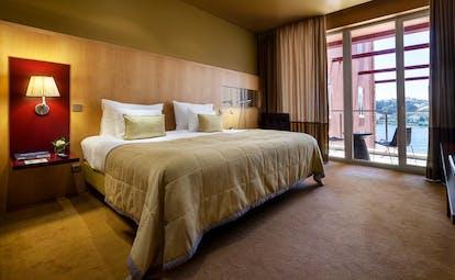 Pestana Palacio do Freixo balcony suite with double bed. leather armchair, french windows leading to blacony