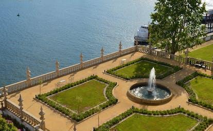 Pestana Palacio do Freixo gardens, manicured lawn in square formation, fountain in centre, wall to river