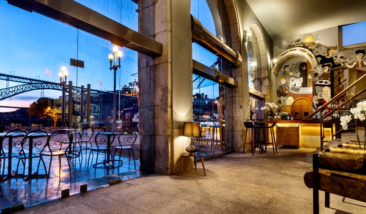 Pestana Vintage Porto bar, stone floors, wooden chairs, colourful wall mural