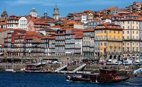 Pestana Vintage Porto exterior, yellow historic building, river bank, boats on the river