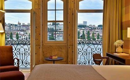 Pestana Vintage Porto grand view room, double bed, historic walls leading to balcony