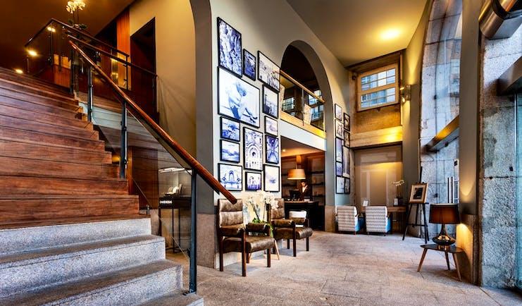 Pestana Vintage Porto lobby, large staircase, historic architecture, armchairs, stone floor