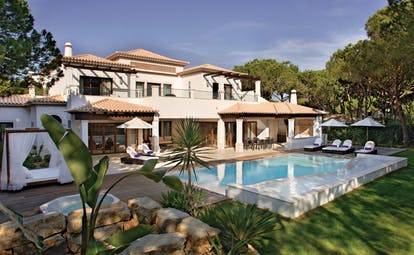 Pine Cliffs Portugal exterior white villa with outdoor pool and sun loungers on deck