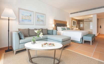 Pine Cliffs Portugal Ocean Suite open plan suite with bed and sitting area with sofa