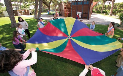 Pine Cliffs Residence Portugal kids club games children playing with colourful sheet in front of pirate ship
