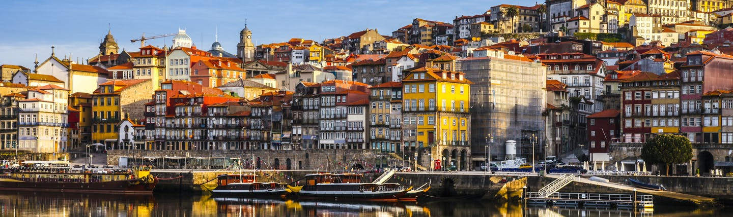 Porto Ribeira in Portugal, colourful houses reflected in the water of the Douro River