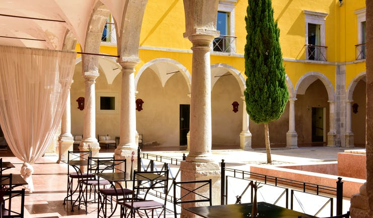 Pousada Convento de Tavira cloisters, outdoor seating, colonnaded cloisters surrounding courtyard with tree