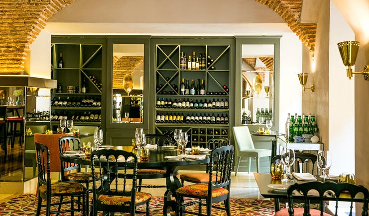 Pousada de Lisboa restaurant, arched ceilings in brown bricks, tables and chairs, large wine cupboard