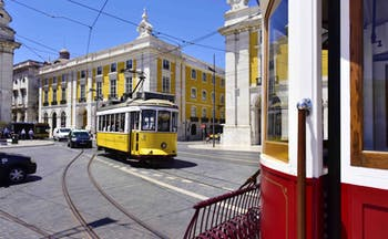 Yellow and white tram in road in front of yellow and white ornate building in Lisbon