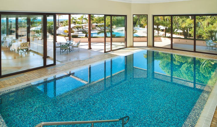 Quinta do Lago Portugal indoor pool with large windows and view of outdoor pool