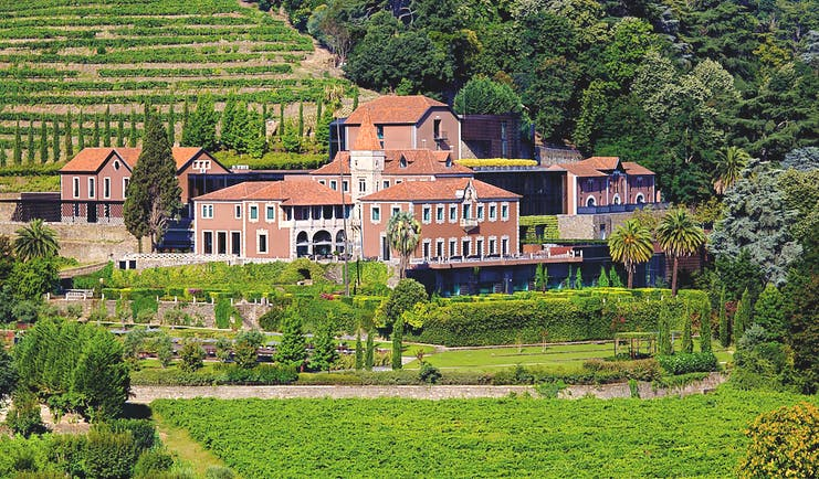 Six Senses Douro Valley Portugal exterior aerial view of a complex of buildings on a wooded hill