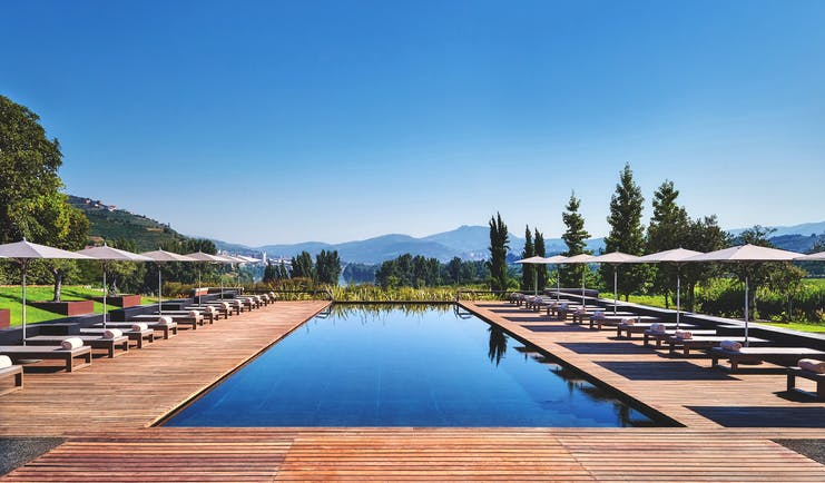 Six Senses Douro Valley Portugal outdoor pool with decked area sun loungers and umbrellas