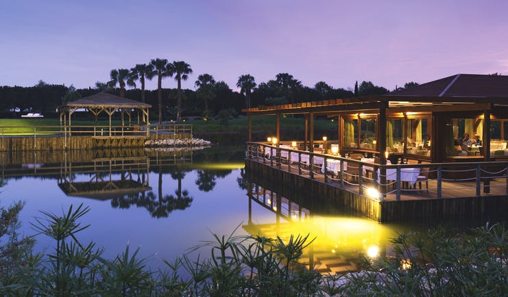 The Lake Spa restaurant building and decking over pond, tables and chairs,
