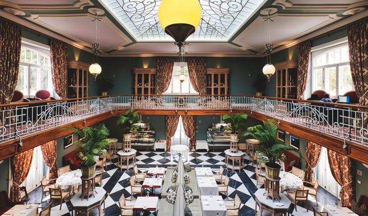 Vidago Palace Portugal winter garden restaurant indoor dining room with balcony glass ceiling and black and white tiles