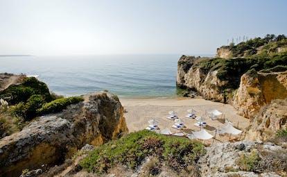 Vila Vita Parc Portugal beach cove with umbrellas and loungers