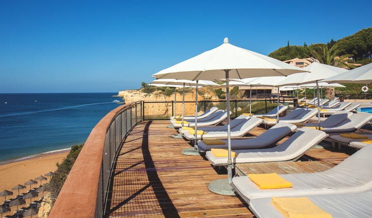 View of the pool deck looking over the beach with white umbrellas and sunbeds on a wooden deck