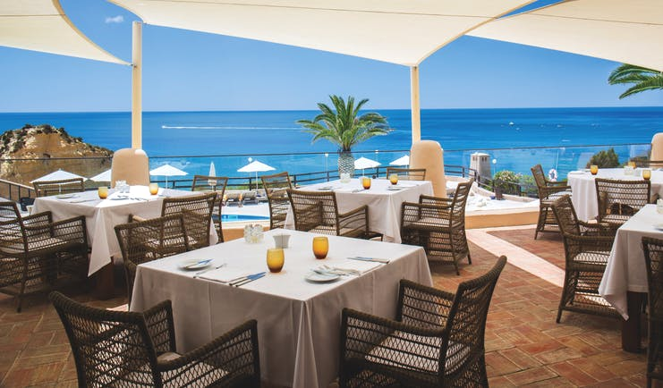dining area restaurant with tables and chairs set out on a terrace overlooking the pool and beach