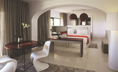 Suite at the vilalara thalassa resort in portugal with a grey and white colour scheme, large double bed and chairs