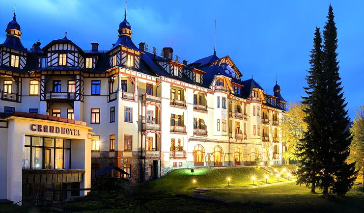 Grandhotel Stary Smokovec exterior, grand hotel building at night, lit up front lawn, trees