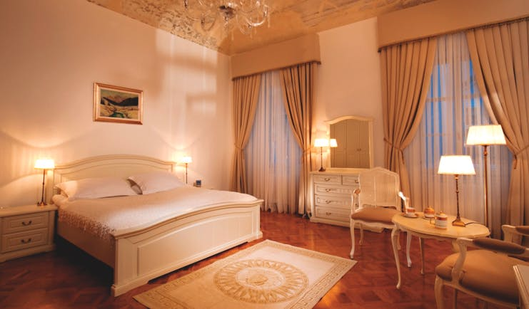 Antiq Palace Hotel Ljubljana bedroom dresser and mirror large windows and a chandelier