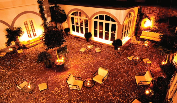 Antiq Palace Hotel Ljubljana courtyard at night time with several chairs and sofas