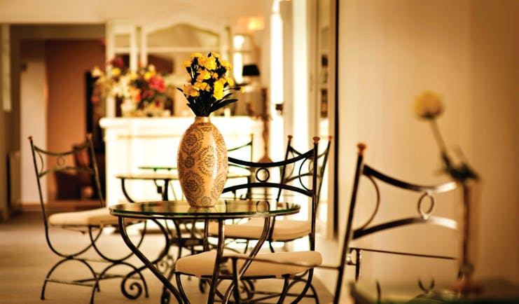 Antiq Palace Hotel Ljubljana lobby with wrought iron chairs vase with yellow flowers