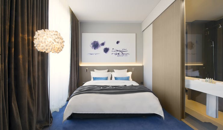 Hotel Cubo double room, bed, painting above bed, bright modern decor
