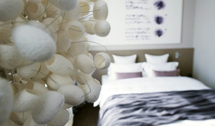 Hotel Cubo guestroom, focus on fake flower installation, double bed, painting, bright modern decor