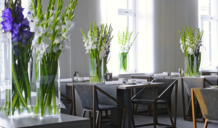 Hotel Cubo restaurant, tables ad chairs, fresh flowers in vases, white bright decor