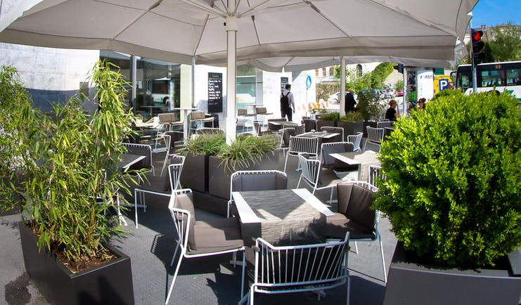 Hotel Cubo terrace, outddor dining area, tables and chairs shaded by umbrellas