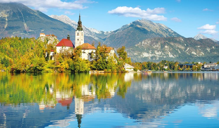 Church on island reflected in blue lake at Lake Bled