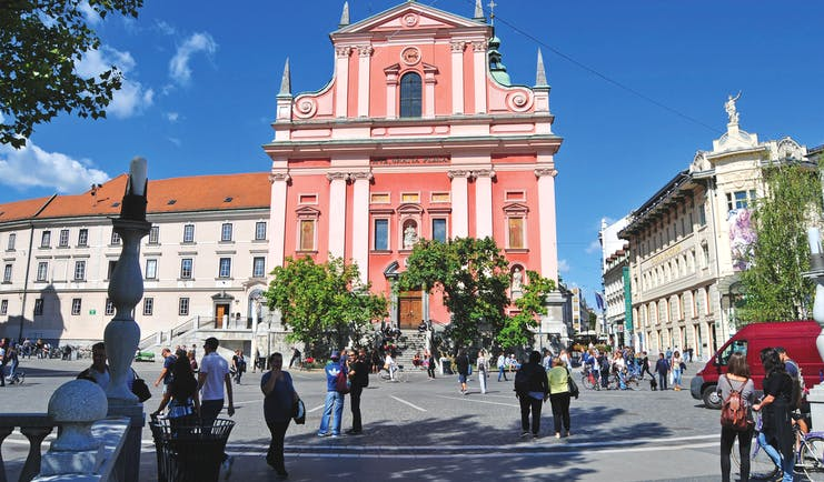 Pink facade of baroque church in square with trees in Ljubljana