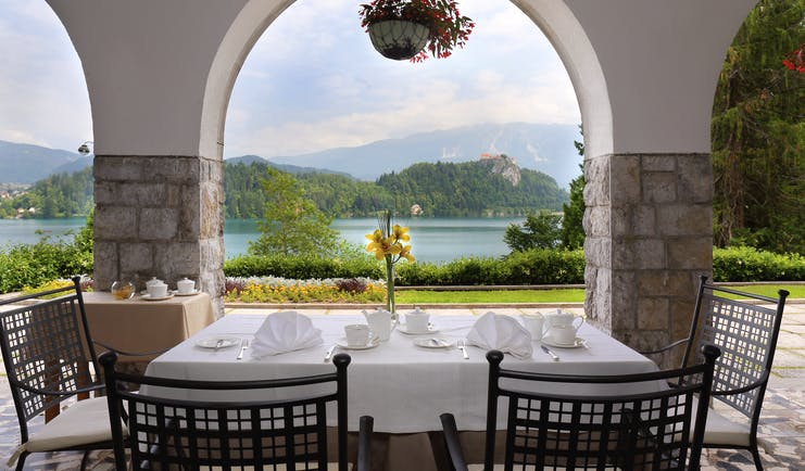 Vila Bled terrace with table and chairs looking through a stone archway onto the lake