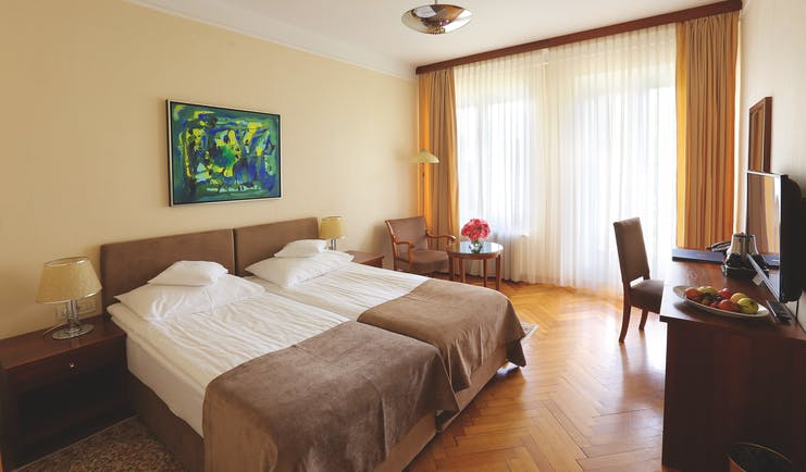 Double room with balcony at the Vila Bled hotel, with a neutral colour scheme and television