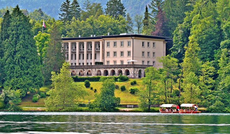 Vila Bled lake view large building with stone archways on a hill above a lake surrounded by trees