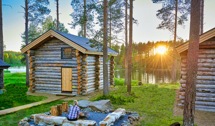 Arctic Retreat cabin exteriors and communal firepit overlooking river, sun setting amongst tall trees