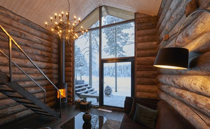 Arctic Retreat cabin interior, sofa, timber walls, modern light fitting