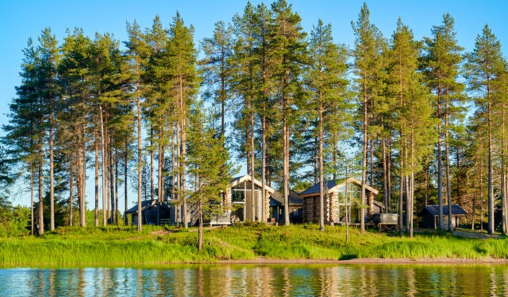 Arctic Retreat cabins overlooking the river, woodland, blue sky