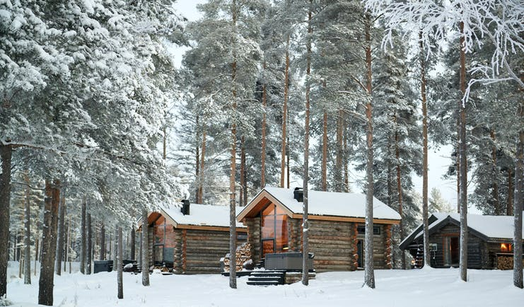 Arctic Retreat cabins exterior, set amongst snowy woodland