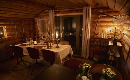 Arctic Retreat dining cabin, cosy lighting, timber walls, table set with candlesticks