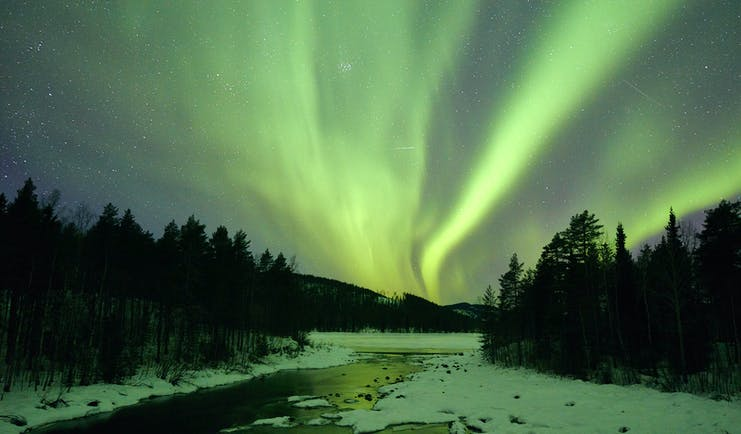 Arctic Retreat northern lights over icy river and woodland