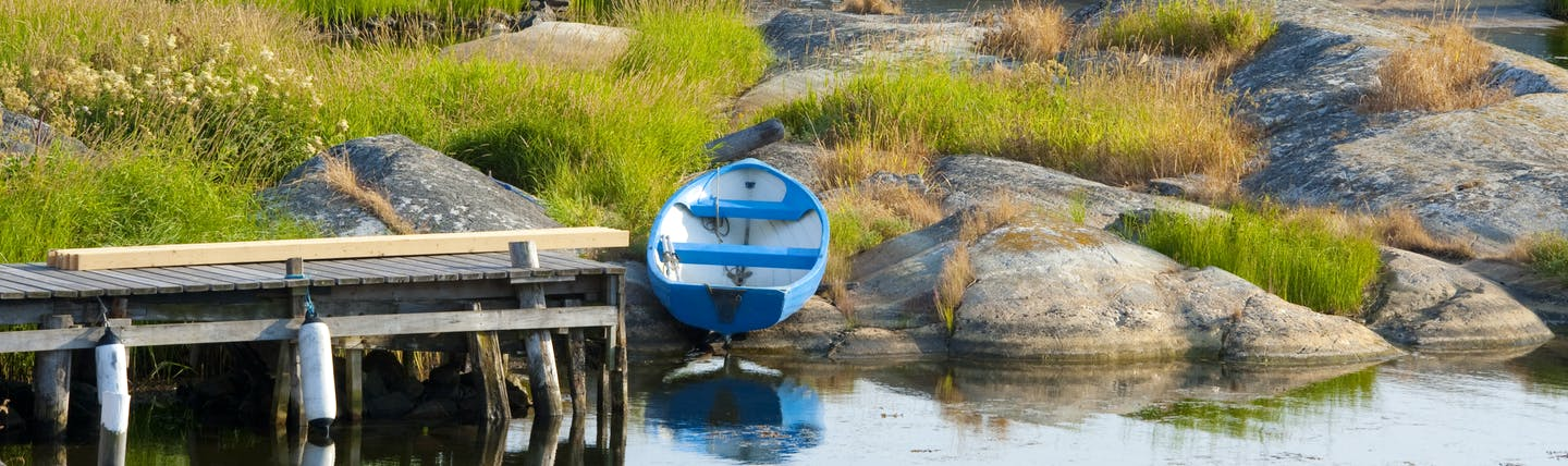 Burnt orange cottages and fishing boats by the water's edge on the Swedish archipelago