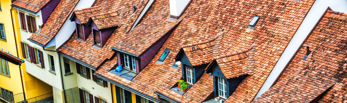 Swiss houses in Bern, traditional architecture, high pointed roofs, shuttered windows, coloured walls