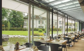 Hotel Allegro Bern restaurant Giardino dining area with large windows looking onto a pond and garden area