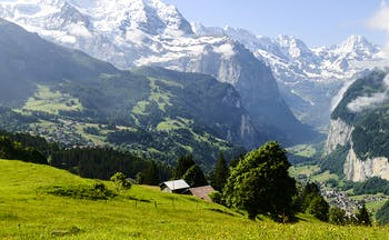 View of Swiss mountain scenery with pastures, village and clouds over mountains