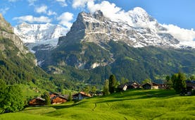 Mountainside villages in Bernese Oberland, wooden lodges, verdant lawns, snow capped mountains